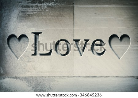 Engraving spelling the word Love on textured old surface - stock photo