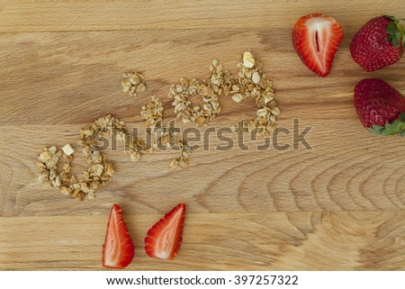 enjoy lettering from muesli and strawberries, a delicious dessert with berries and cookies, healthy Breakfast on wooden background, close-up - stock photo