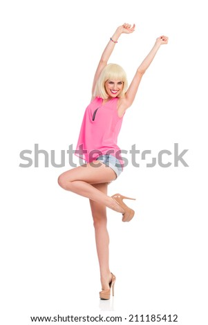 Enjoy the day. Smiling blond young woman in high heels and pink top standing on one leg with arms raised. Full length studio shot isolated on white. - stock photo