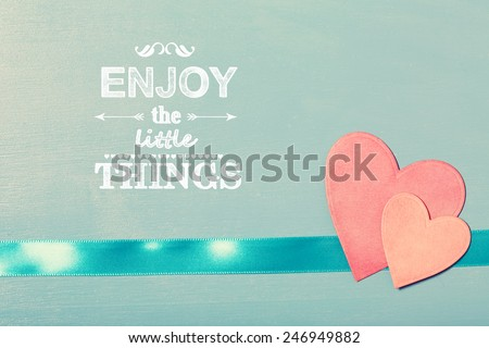 Enjoy the Little Things text with pink paper hearts on blue wooden board - stock photo