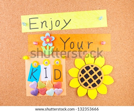 Enjoy your kid, words and decoration on cork - stock photo