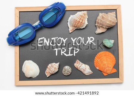 Enjoy Your Trip text on chalk board with swimming goggle and shell - vacation and business concept - stock photo