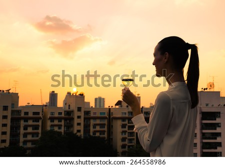 Enjoying a glass of wine and the city view. - stock photo