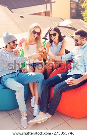 Enjoying beer with friends. Top view of four young cheerful people cheering with beer and smiling while sitting at the bean bags on the roof of the building - stock photo