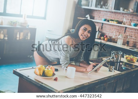 Enjoying carefree morning. Attractive young mixed race woman leaning at the kitchen desk and smiling while holding digital tablet - stock photo