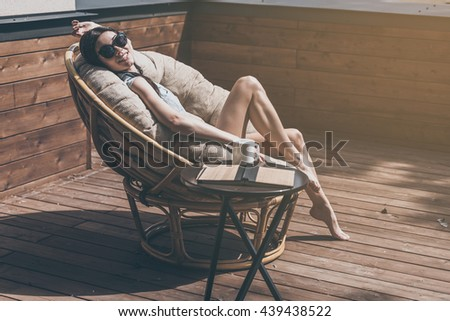 Enjoying carefree time. Beautiful young smiling woman relaxing in a big comfortable chair on her outdoor house terrace  - stock photo