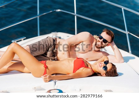 Enjoying carefree time together. Smiling young couple sunbathing while lying on the deck of yacht  - stock photo