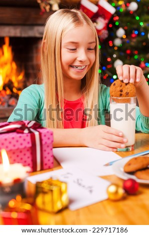 Enjoying Christmas cookies. Cute little girl soaking cookie in milk and smiling while sitting at the table with Christmas Tree and fireplace in the background  - stock photo