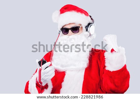 Enjoying Christmas music. Santa Claus in sunglasses and headphones listening to MP3 Player and gesturing while standing against grey background - stock photo