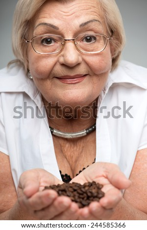 Enjoying coffee aroma. Closeup of smiling senior woman showing coffee beans in her palms while standing against grey background - stock photo