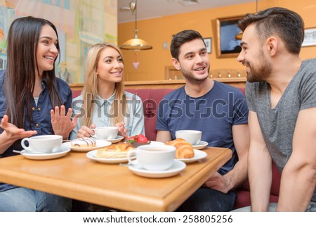 Enjoying coffee with great people. Four friends laughing and drinking coffee while having breakfast in the cafe  - stock photo