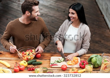 Enjoying cooking together. Top view of beautiful young couple preparing healthy salad together and smiling - stock photo