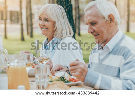 Enjoying dinner on fresh air. Senior couple enjoying meal together while sitting at the dining table outdoors - stock photo