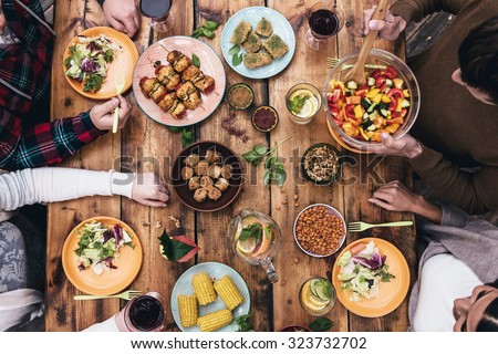 Enjoying dinner together. Top view of four people having dinner together while sitting at the rustic wooden table - stock photo
