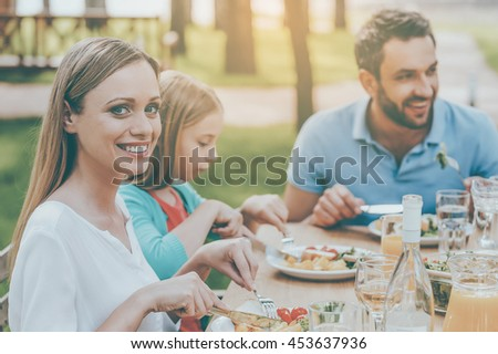 Enjoying dinner with family. Happy family enjoying meal together while woman looking at camera and smiling - stock photo