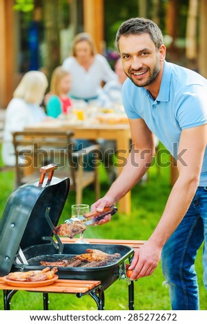 Enjoying family barbecue. Happy young man barbecuing meat on the grill and smiling while other members of family sitting at the dining table in the background  - stock photo