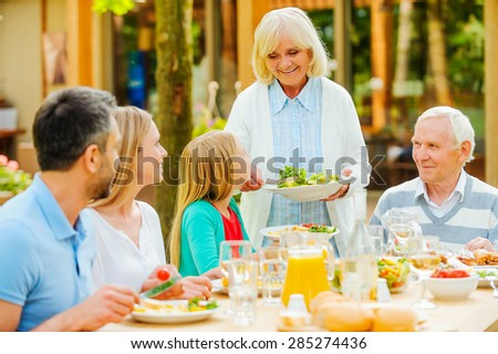 Enjoying family time. Happy family of five people enjoying meal together while sitting at the dining table outdoors  - stock photo