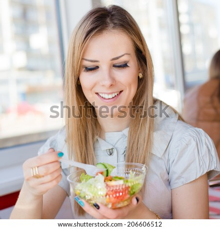 enjoying fast food: close up portrait of eating delicious salad beautiful young woman cute blond girl having fun in restaurant or coffee shop happy smiling picture