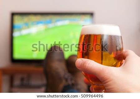 enjoying football game with glass of beer