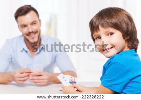 Enjoying free time together. Happy father and son playing cards and smiling  - stock photo