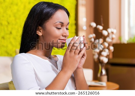 Enjoying fresh coffee. Side view of beautiful young African woman holding coffee cup near nose and smiling while keeping eyes closed and sitting at the chair at home - stock photo