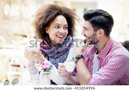 Enjoying fresh coffee together. Shot of beautiful young couple looking at each other and smiling while enjoying coffee in cafe together - stock photo