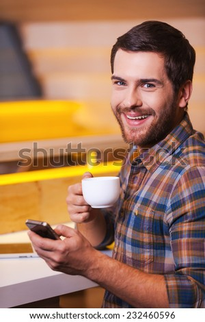 Enjoying fresh made coffee. Cheerful young man holding mobile phone and drinking coffee while sitting in cafe - stock photo