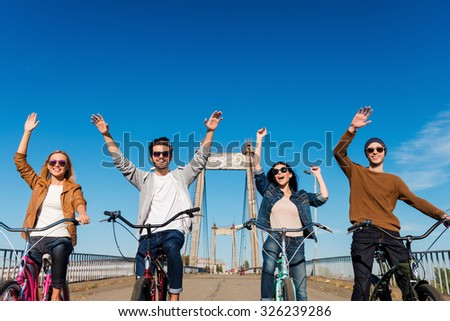 Enjoying fun ride. Low angle view of four young cheerful people riding their bicycles and keeping arms raised - stock photo