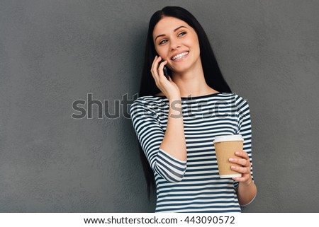 Enjoying good talk and hot drink. Attractive young woman holding coffee cup and smiling while talking on the mobile phone and standing against grey background - stock photo