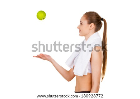Enjoying healthy lifestyle. Side view of beautiful young woman throwing a green apple up and smiling while standing isolated on white - stock photo