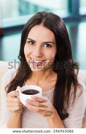 Enjoying her coffee break. Top view of attractive young woman holding cup with coffee and smiling while relaxing on the couch at home  - stock photo