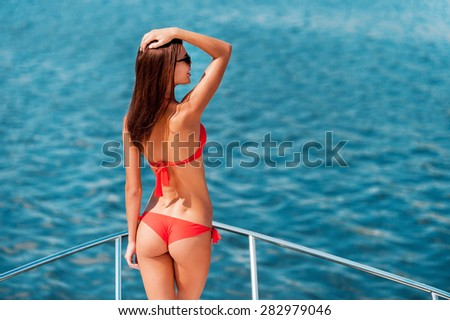 Enjoying her great summer vacation. Rear view of young woman in bikini holding hand in hair and looking away while standing on the ship's bow   - stock photo