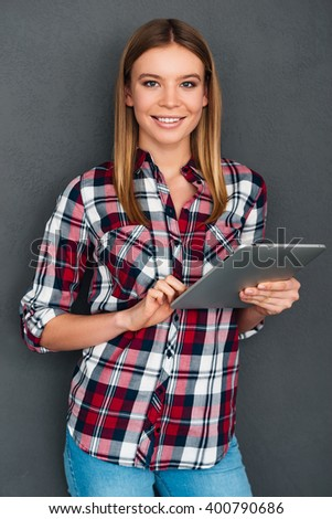 Enjoying her new digital tablet. Beautiful young woman using her digital tablet and looking at camera with smile while standing against grey background - stock photo