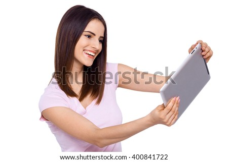 Enjoying her new tablet. Beautiful cheerful young woman using her touchpad with smile on white background - stock photo
