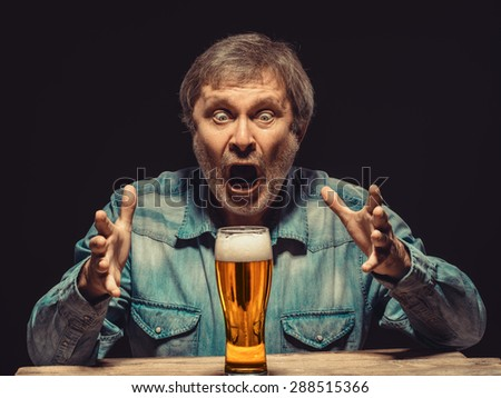 Enjoying his favorite beer.  The front view of handsome screaming man as fan in denim shirt with glass of beer, sitting at the wooden table. Concept of enthusiasm and ecstasy - stock photo