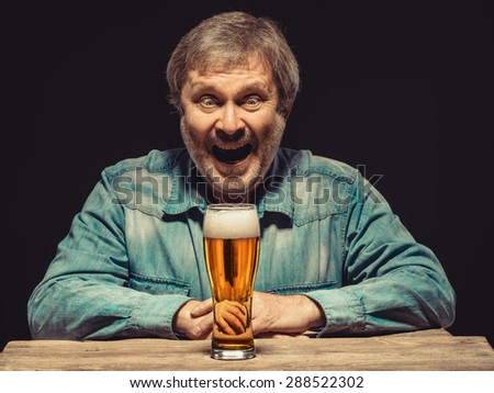 Enjoying his favorite beer.  The front view of handsome smiling  man as fan in denim shirt with glass of beer, sitting at the wooden table. Concept of enthusiasm and ecstasy - stock photo