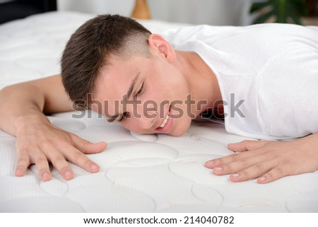 Enjoying his mattress. Young man lying on the bed. Quality mattress. - stock photo