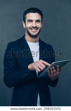 Enjoying his new digital tablet. Cheerful young man holding digital tablet and smiling while standing against grey background - stock photo