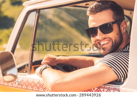 Enjoying his road trip. Cheerful young man smiling at camera and holding hand on steering wheel while sitting inside of his minivan - stock photo