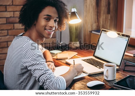 Enjoying his study. Side view of cheerful young African man writing something in his notebook and looking at camera with smile while sitting at his working place - stock photo