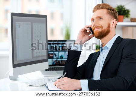 Enjoying his work. Happy young bearded businessman talking on the mobile phone and writing in note pad while sitting at his working place - stock photo