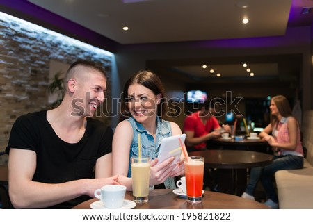 Enjoying in nightlife. Couple enjoying in evening. Drinking coffee and lemonade. Using tablet and smiling.
