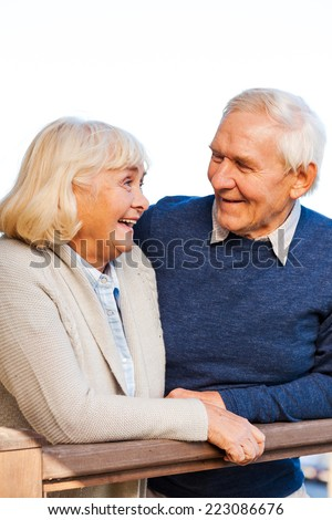 Enjoying life together. Happy senior couple looking at each other and smiling while standing outdoors - stock photo