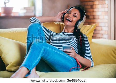 Enjoying music at home. Happy young woman adjusting her headphones and keeping eyes closed while lying on the couch at home - stock photo