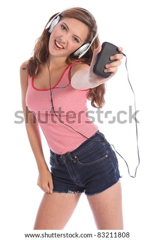 Enjoying music on her headphones from mobile smart phone, for a beautiful young teenager school girl 16, with long brown hair wearing a red and white vest. Studio portrait against white background. - stock photo