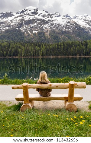 enjoying nature, girl sitting on a bench near the lake and looks on big mountains