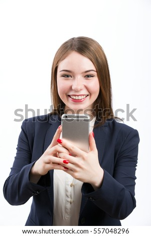 Enjoying productive day. Young successful business woman in formal wear using mobile phone and smiling to camera, standing over white isolated background, copy space