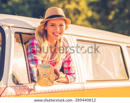 Enjoying road trip. Beautiful young woman looking at camera and smiling while looking through the vehicle window - stock photo