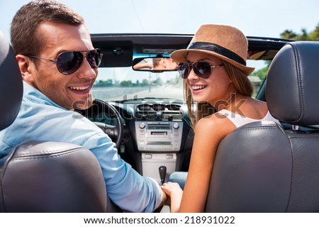 Enjoying road trip together. Beautiful young couple enjoying road trip in their convertible and looking over shoulder with smile - stock photo