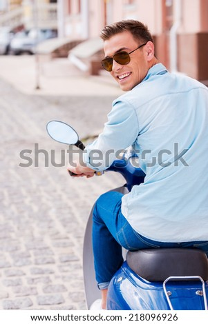 Enjoying scooter ride. Rear view of cheerful young man in sunglasses riding scooter along the street and looking over shoulder - stock photo